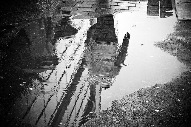 An image of the person's reflection in a puddle. Using reflection in photography is one of the well-known tips for street photographers.
